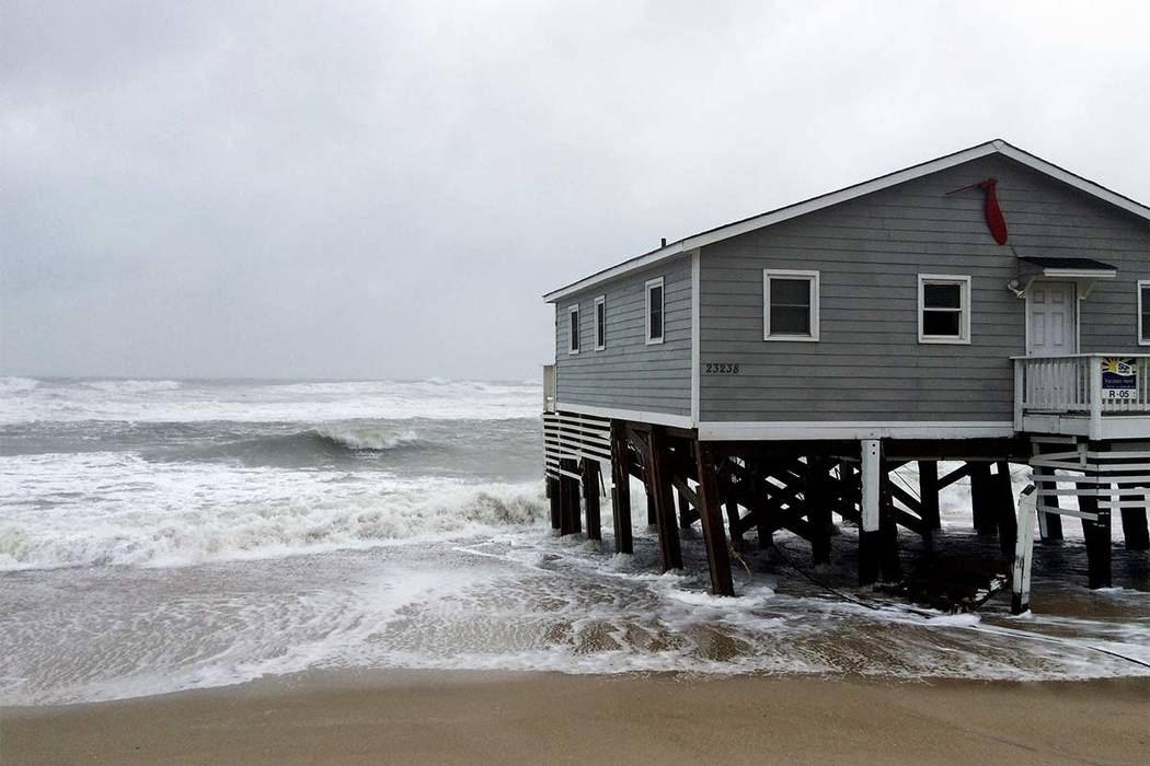 Waves wash ashore hitting a house as winds and storm surge from Tropical Storm Maria lash North Carolinas Outer Banks as the storm moves by well off-shore on Wednesday, Sept. 27, 2017. (Ben Finley/AP)