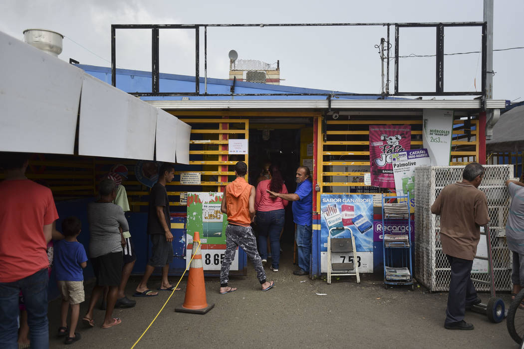 Residents from Juana Matos wait in line to buy groceries at Catano Mini Market in the middle of a supply shortage caused by the passage of Hurricane Maria, in Catano, Puerto Rico, Wednesday, Septe ...