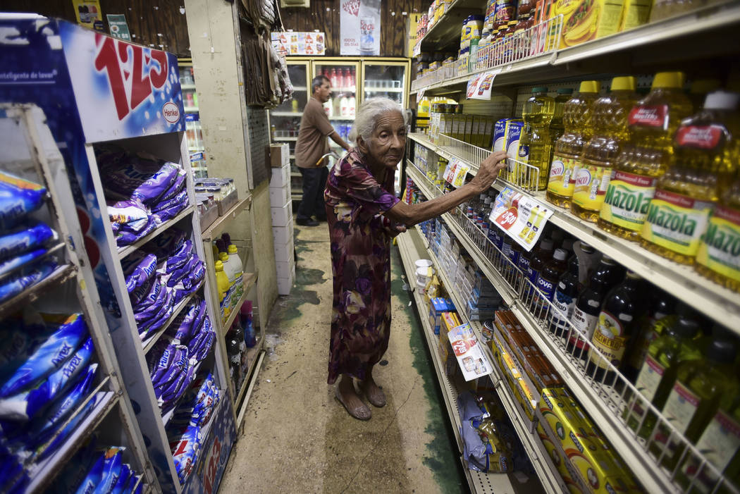 Residents from Juana Matos buy groceries at Catano Mini Market in the middle of a supply shortage caused by the passage of Hurricane Maria, in Catano, Puerto Rico, Wednesday, Sept. 27, 2017. Since ...