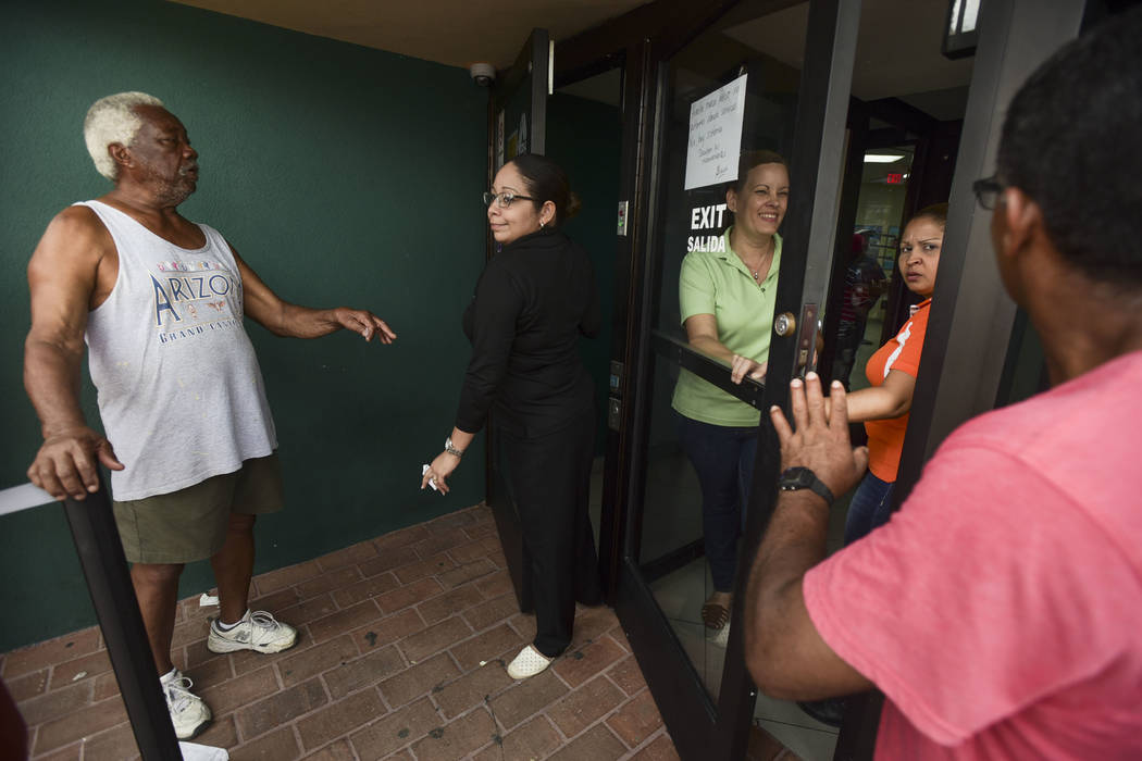 Clients of Coopaca Coperative wait in line to withdraw cash from their accounts after the passage of Hurricane Maria a week ago, in Catano, Puerto Rico, Wednesday, Sept. 27, 2017. The cooperative  ...