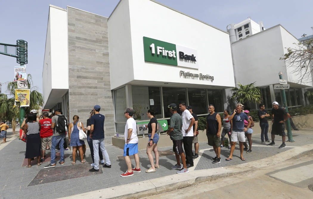 People wait in line to withdraw cash at a bank in the aftermath of Hurricane Maria, in San Juan, Puerto Rico, Wednesday, Sept. 27, 2017. A week since the passing of Maria many are still waiting fo ...
