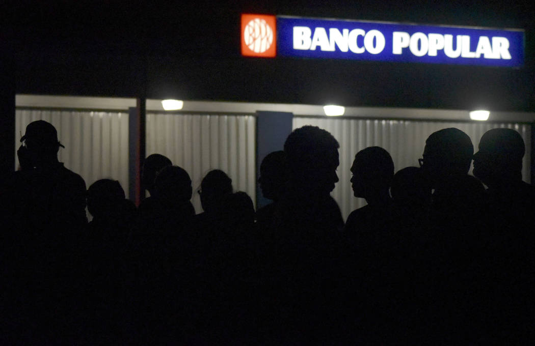 Clients of Popular Bank of Puerto Rico wait in line at the Carolina Shopping Court branch to withdraw cash from their accounts after the passage of Hurricane Maria, in Carolina, Puerto Rico, Wedne ...