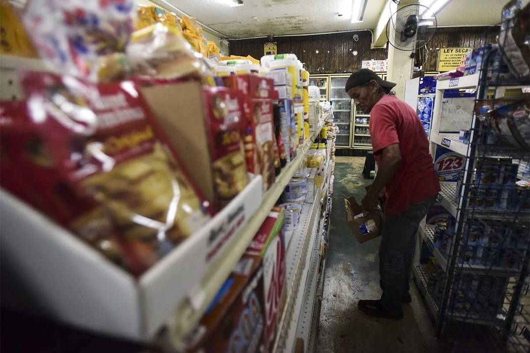 Residents from Juana Matos buy groceries at Catano Mini Market in the middle of a supply shortage caused by the passage of Hurricane Maria, in Catano, Puerto Rico, Wednesday, Sept. 27, 2017. T (AP ...