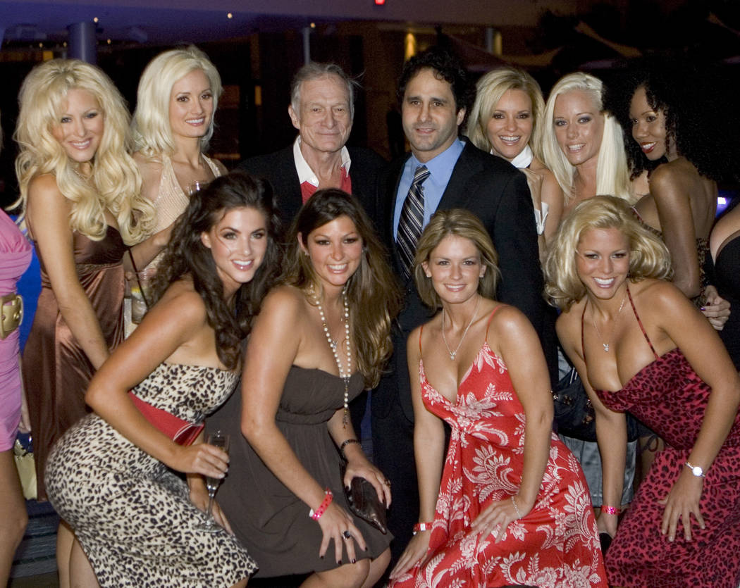 Playboy founder Hugh Hefner and George Maloof pose with photos with Playboy playmates and Hefner's girlfriends during a party to celebrate the opening of the Playboy Club located in the new Fantas ...