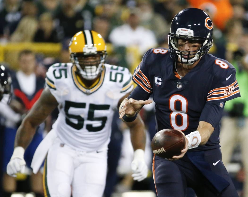 Chicago Bears' Mike Glennon hands off in front of Green Bay Packers' Ahmad Brooks during the first half of an NFL football game Thursday, Sept. 28, 2017, in Green Bay, Wis. (AP Photo/Mike Roemer)