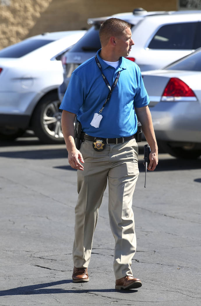 A detective with the Metropolitan Police Department prepares to push back members of the media as Metro investigates an officer-involved shooting that occurred in a strip mall near Jones Boulevard ...