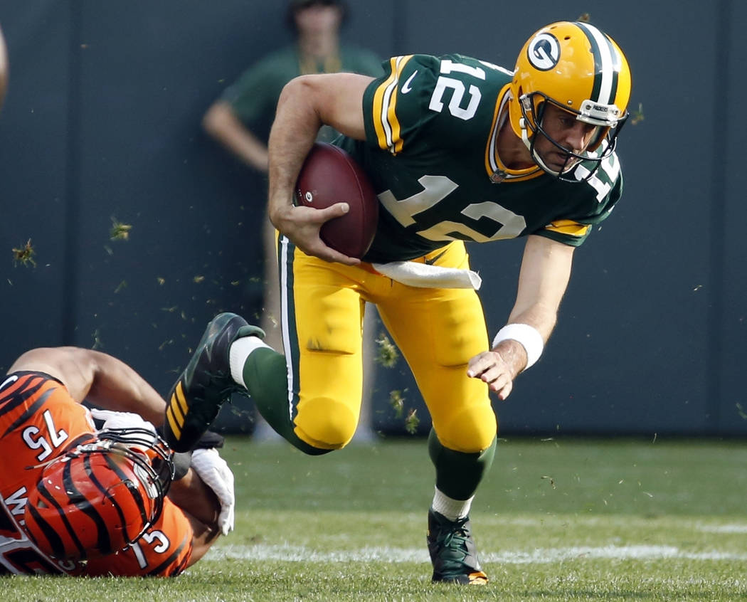 FILE - In this Sunday, Sept. 24, 2017, file photo, Green Bay Packers' Aaron Rodgers tries to get away from Cincinnati Bengals' Jordan Willis during the first half of an NFL football game in Green  ...