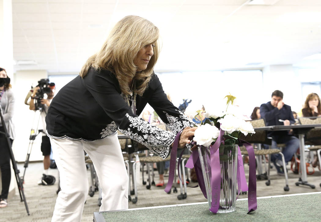 Peggy Wellman of the Metropolitan Police Department's victim services, places a rose at Metro's headquarters in Las Vegas on Wednesday, Sept. 27, 2017, during the annual ceremony to remember victi ...