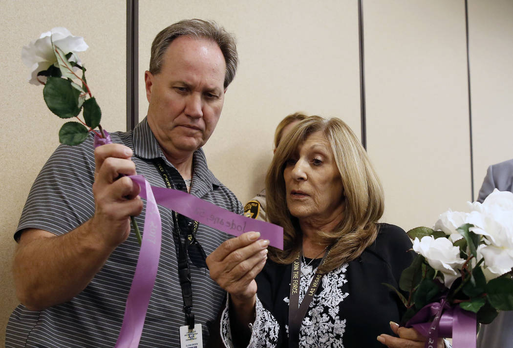 Officer Glenn Brook of the Metropolitan Police Department and Peggy Wellman of Metro's victim services read a name of a domestic violence victim on a ribbon at Metro's headquarters in Las Vegas on ...