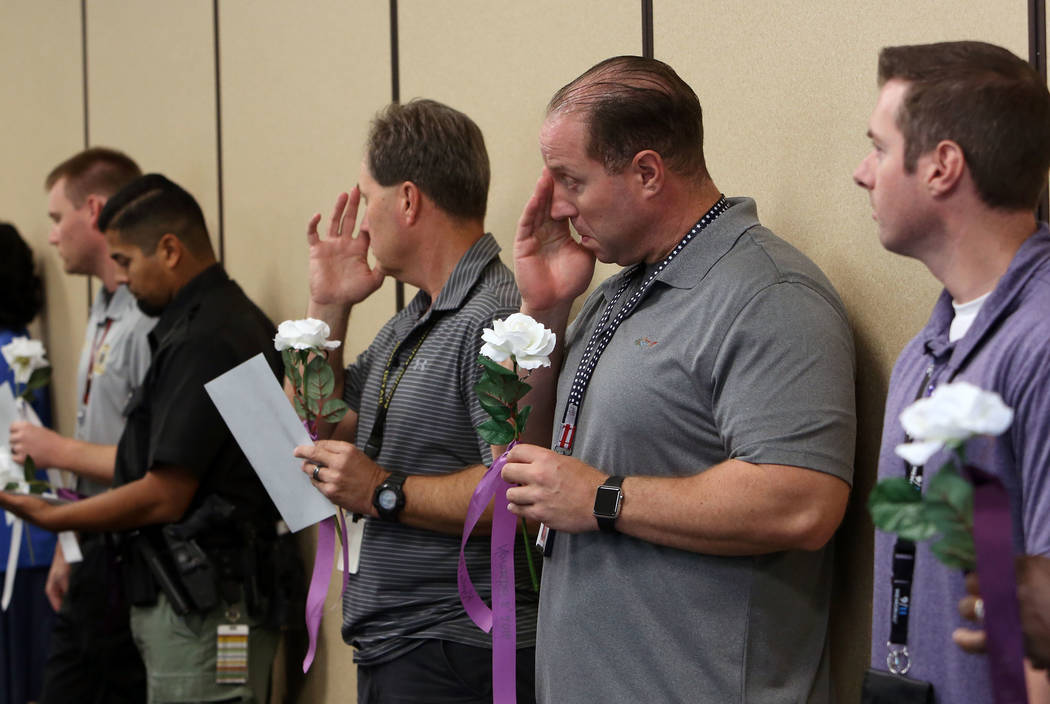 Roger Price, second from right, and Glenn Brook, third from right, both from the Metropolitan Police Department, attend the annual ceremony to remember victims of domestic violence at Metro's head ...