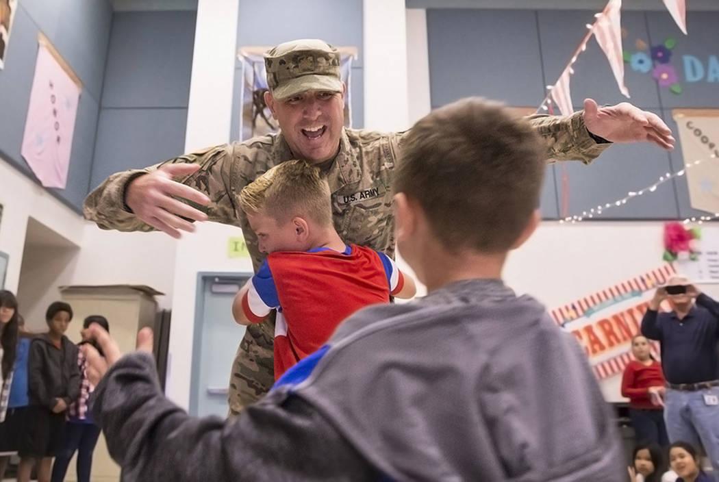 Maj. Beau Vinatieri gets a big hug from son's Jeau, 10, and Keaul, 8, in a surprise ceremony at Bunker Elementary School on Thursday, Nov. 10, 2016, in Las Vegas.  Maj. Vinatieri recently returned ...