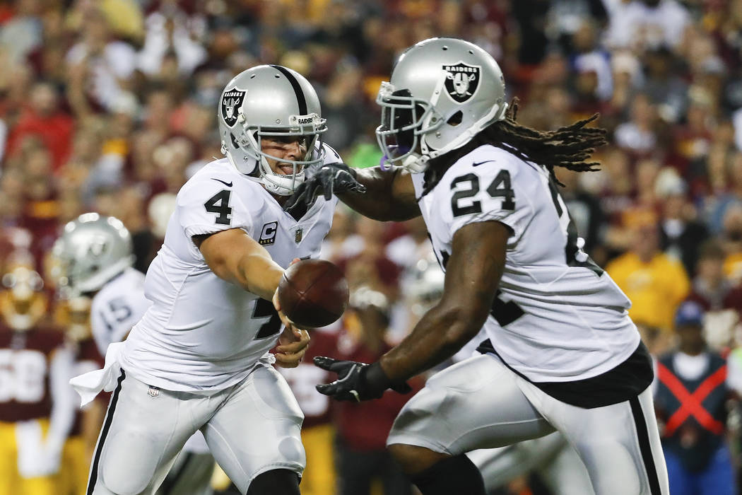 Oakland Raiders quarterback Derek Carr (4) hands the ball to running back Marshawn Lynch (24) during the first half of an NFL football game against the XXX in Landover, Md., Sunday, Sept. 24, 2017 ...