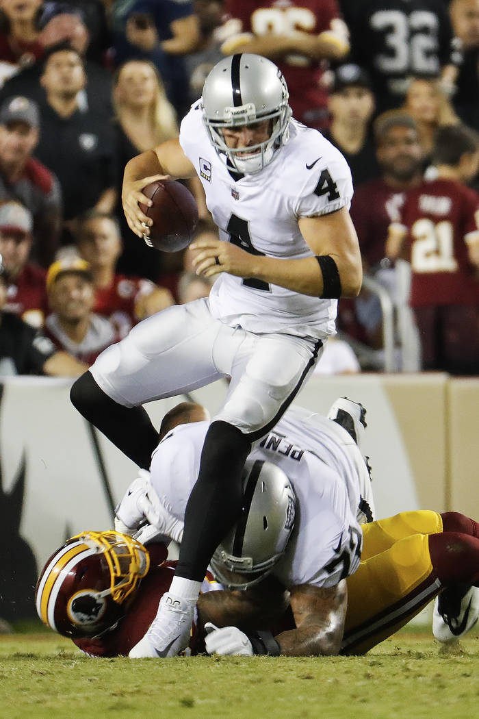 Oakland Raiders quarterback Derek Carr (4) is sacked by Washington Redskins outside linebacker Preston Smith (94) during the first half of an NFL football game in Landover, Md., Sunday, Sept. 24,  ...