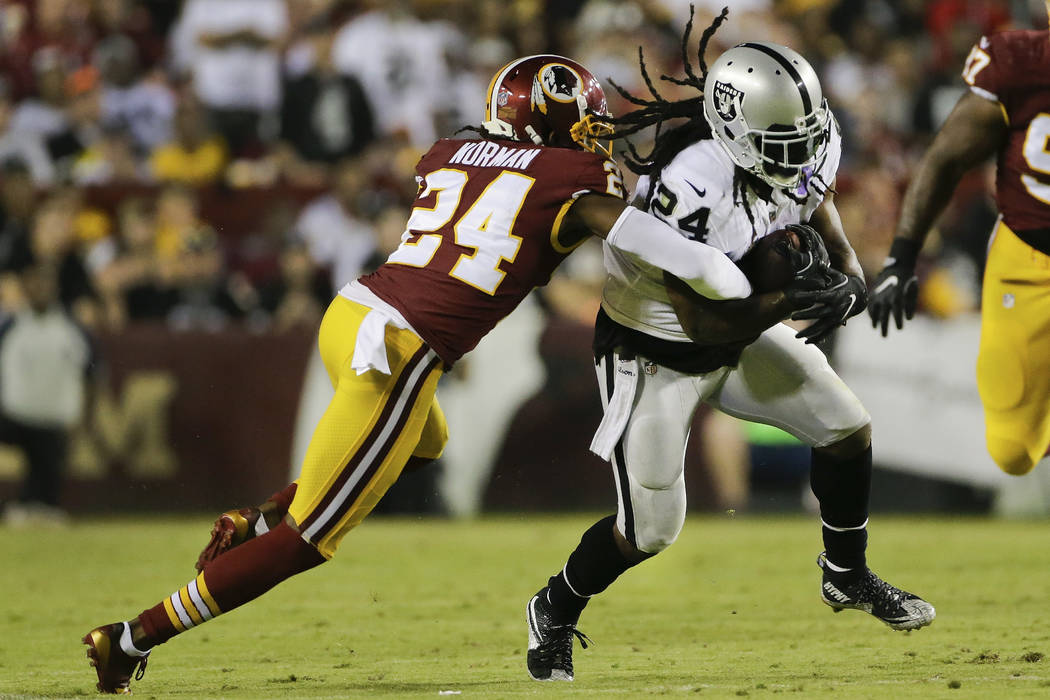 Washington Redskins cornerback Josh Norman, left, stops Oakland Raiders running back Marshawn Lynch (24) during the first half of an NFL football game in Landover, Md., Sunday, Sept. 24, 2017. (AP ...