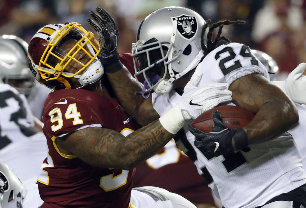 Washington Redskins outside linebacker Preston Smith (94) tackles Oakland Raiders running back Marshawn Lynch (24) during an NFL football game Sunday, Sept. 24, 2017, in Landover, Md. (AP Photo/Al ...