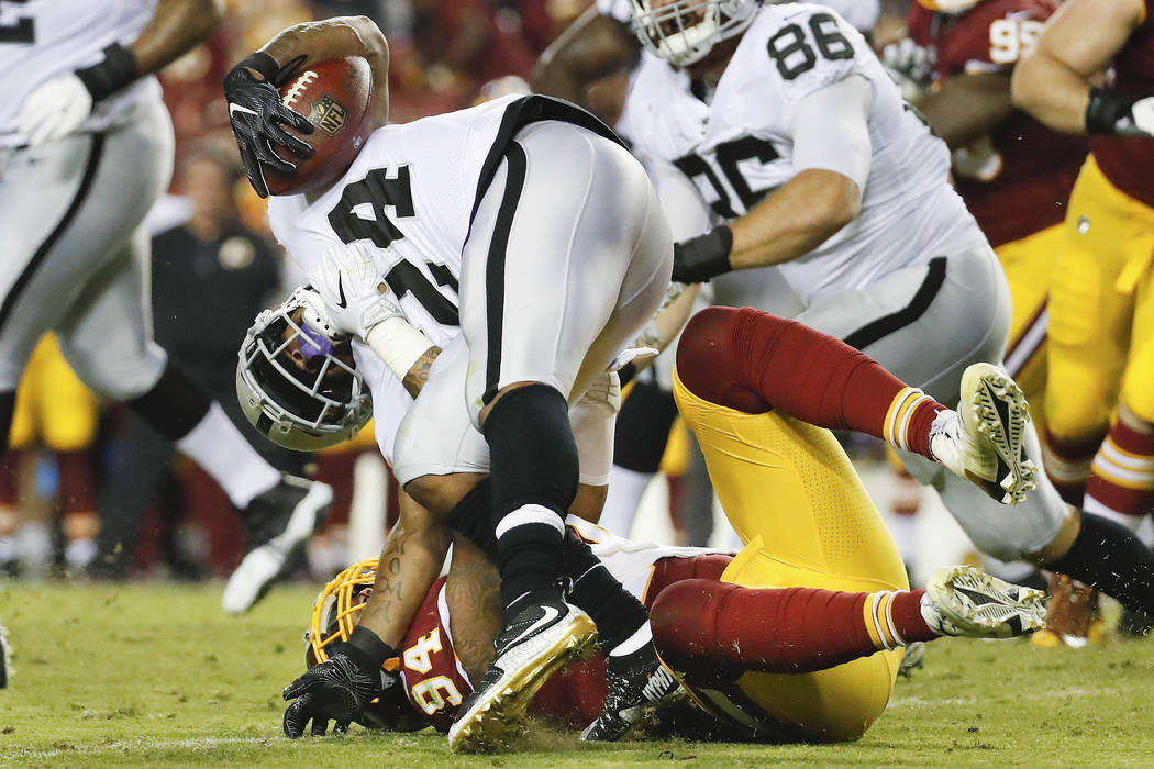 Oakland Raiders running back Marshawn Lynch (24) is stopped by Washington Redskins outside linebacker Preston Smith (94) during the first half of an NFL football game in Landover, Md., Sunday, Sep ...