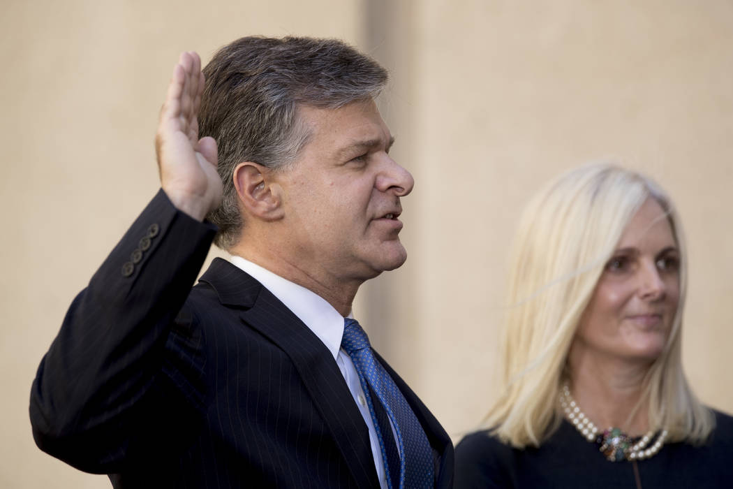 FBI Director Chris Wray, accompanied by his wife Helen garrison Howell, is administered the ceremonial Oath of Office during an installation ceremony for him at the FBI Building, Thursday, Sept. 2 ...