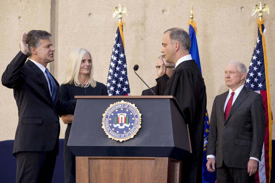 FBI Director Chris Wray, accompanied by his wife Helen Garrison Howell, second from left, and Attorney General Jeff Sessions, right, is administered the ceremonial Oath of Office by U.S. District  ...