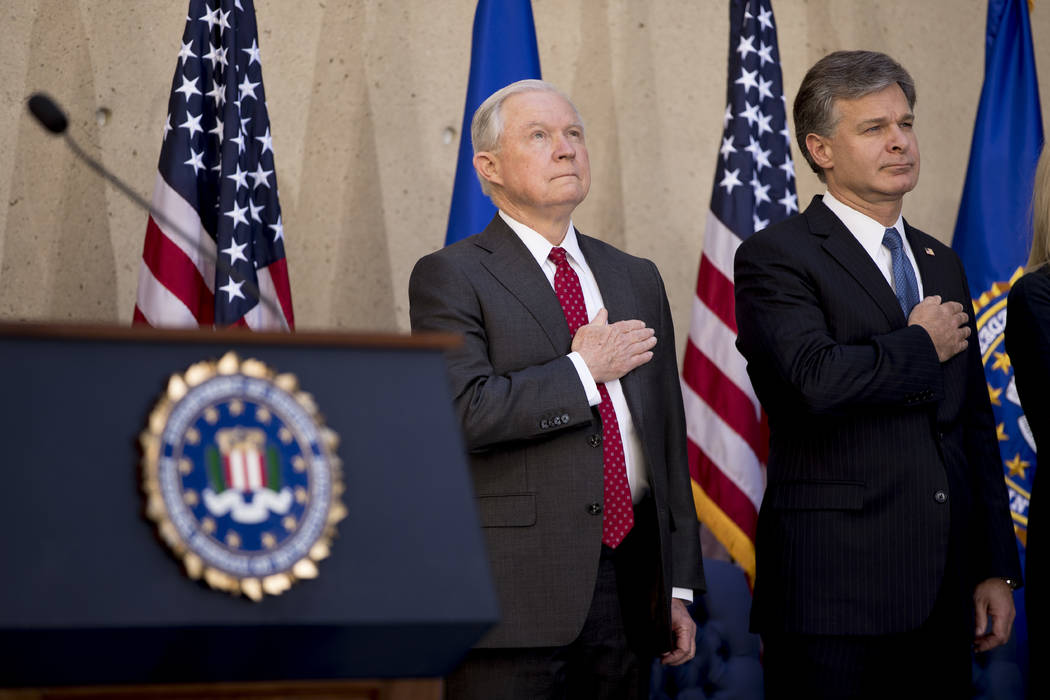 Attorney General Jeff Sessions and FBI Director Chris Wray stand for the National Anthem during an installation ceremony for Wray at the FBI Building, Thursday, Sept. 28, 2017, in Washington. (And ...