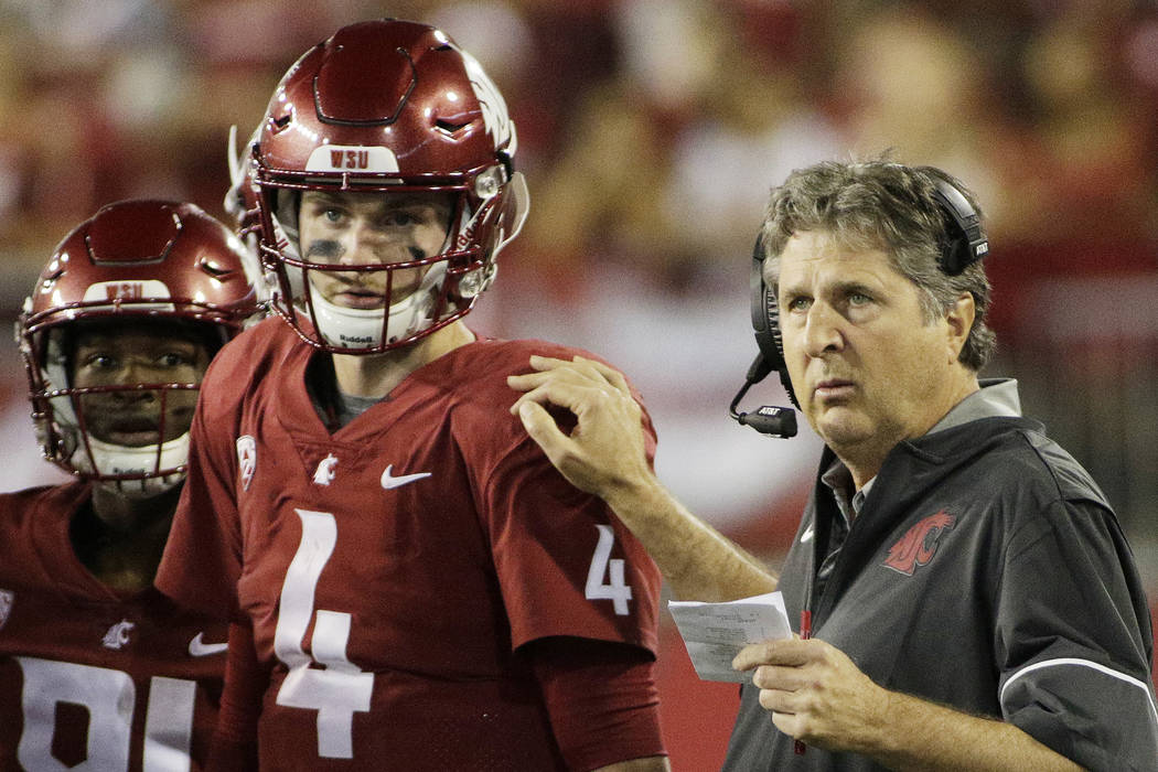Washington State coach Mike Leach, right, speaks with quarterback Luke Falk during the first half of an NCAA college football game against Boise State in Pullman, Wash., Saturday, Sept. 9, 2017. ( ...