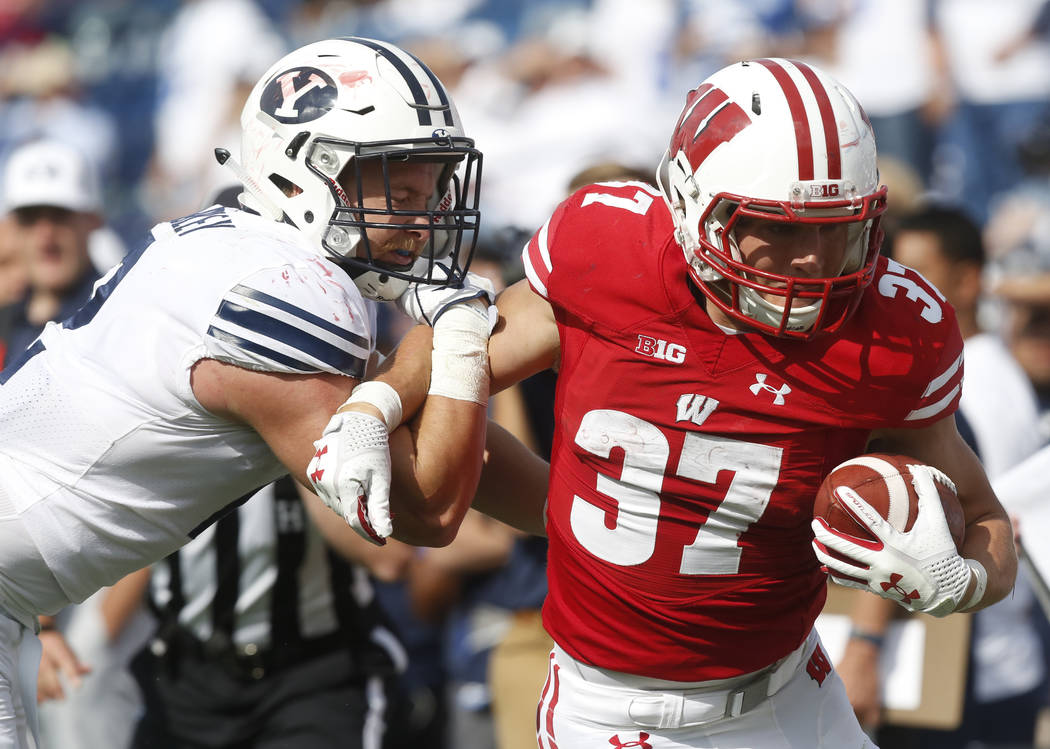 Wisconsin running back Garrett Groshek (37) tries to break free of a tackle by BYU linebacker Matt Hadley (2) while running the ball in the second half during an NCAA college football game, Saturd ...