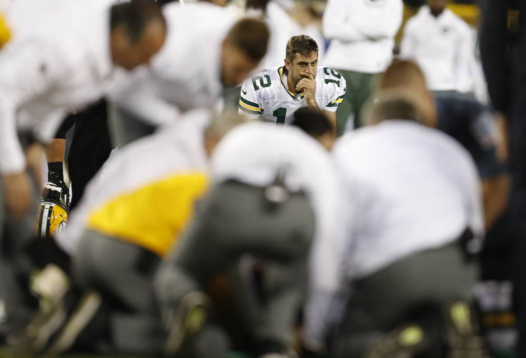 Green Bay Packers' Aaron Rodgers watches as teammate Davante Adams is attended to after being hit in the head during the second half of an NFL football game against the Chicago Bears Thursday, Sep ...