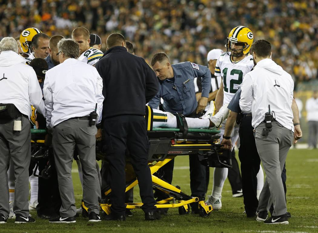 Green Bay Packers' Aaron Rodgers watches as teammate Davante Adams is taken off the field after being hit in the head during the second half of an NFL football game against the Chicago Bears Thurs ...