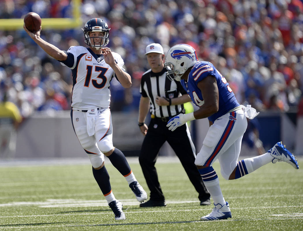 Denver Broncos quarterback Trevor Siemian (13) throws a pass while pressured by Buffalo Bills defensive end Eddie Yarbrough (54) during the first half of an NFL football game, Sunday, Sept. 24, 20 ...