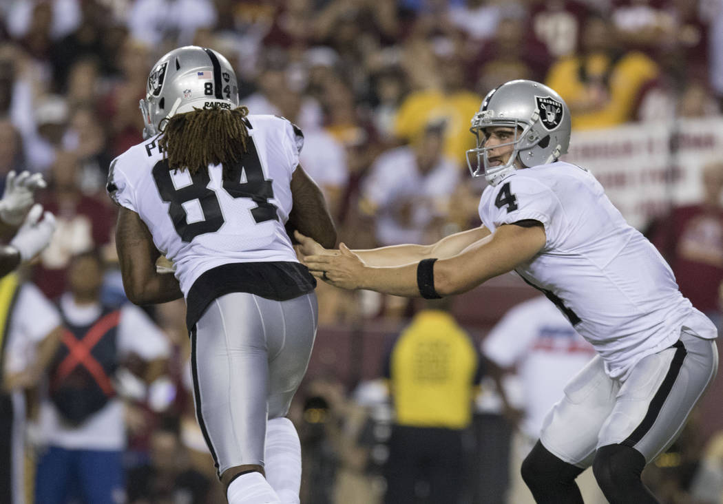 Oakland Raiders quarterback Derek Carr (4) hands off the football to wide receiver Cordarrelle Patterson (84) in the first half of their game against the Washington Redskins in Landover, Md., Sund ...