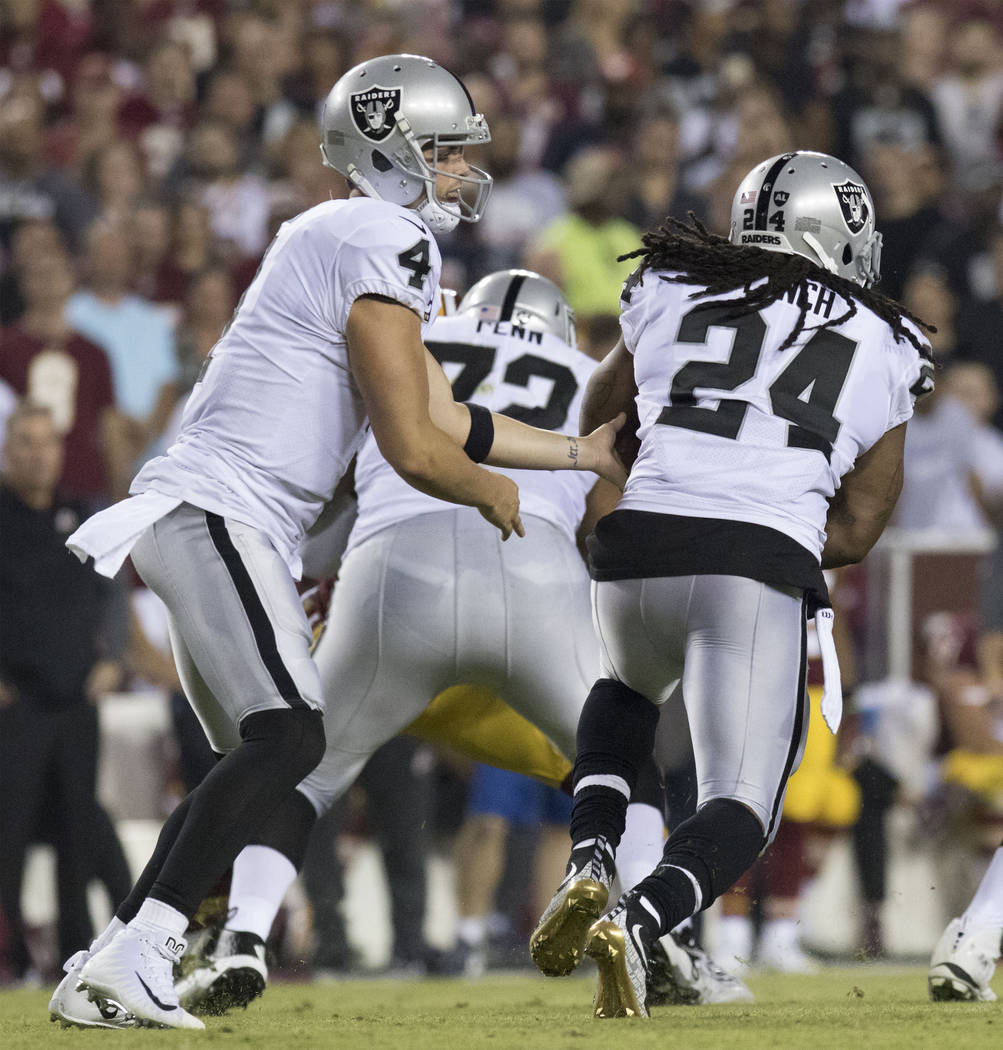 Oakland Raiders quarterback Derek Carr (4) hands off the football to Oakland Raiders running back Marshawn Lynch (24) in the first half of their game against the Washington Redskins in Landover, M ...