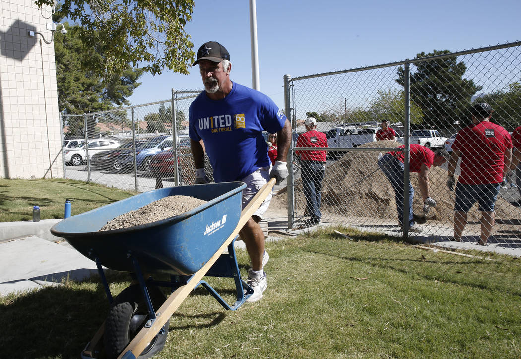 Rick Pollard, volunteer, delivers decorative gravel in a wheelbarrow to Crestwood Elementary School garden as approximately 50 volunteers, helping the local nonprofit Green Our Planet, install a g ...