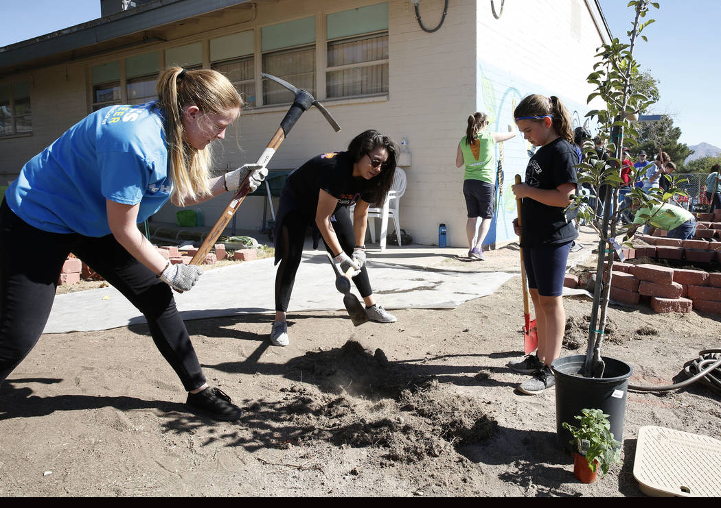 Amanda Konold, left, and Randi Fisher, both volunteers, dig the ground as Crestwood Elementary School student Savannah Foschetti, righ, looks on as approximately 50 volunteers, helping the local n ...