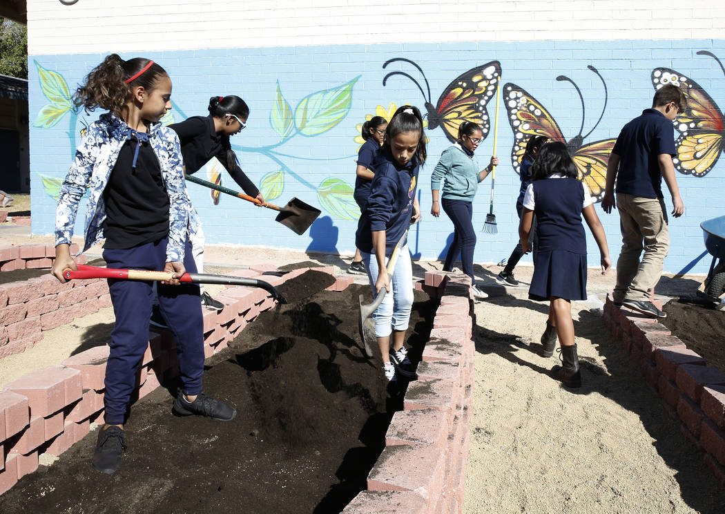 Crestwood Elementary School students Jadhira Alvarez, left, and Kimberly Rivera spread fertile soil as approximately 50 volunteers, helping the local nonprofit Green Our Planet, install a garden a ...