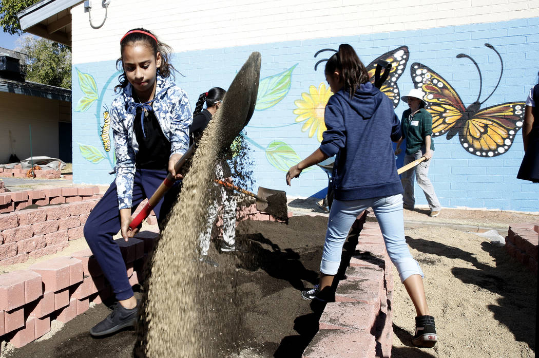 Crestwood Elementary School student, Jadhira Alvarez, spreads fertile soil as approximately 50 volunteers, helping the local nonprofit Green Our Planet, install a garden at her school as part of t ...