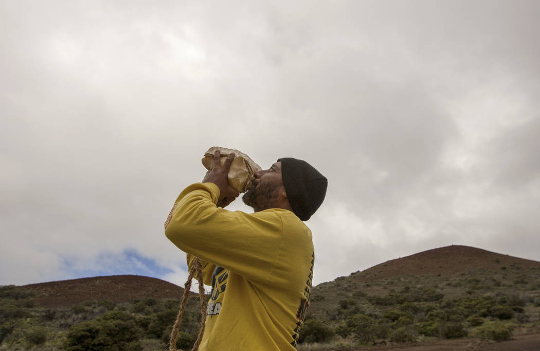 Kupono Mele-Ana-Kekua, 35, of Kaaaawa, Hawaii, blows a conch shell near the summit of Mauna Kea on Hawaii's Big Island in 2015. (AP Photo/Caleb Jones, File)