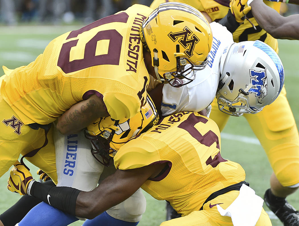 Minnesota defensive kick off coverage players Gary Moore, top, and Trenton Guthrie combine to stop Middle Tennessee kick returner Shane Tucker on the runback in the first half of an NCAA college f ...