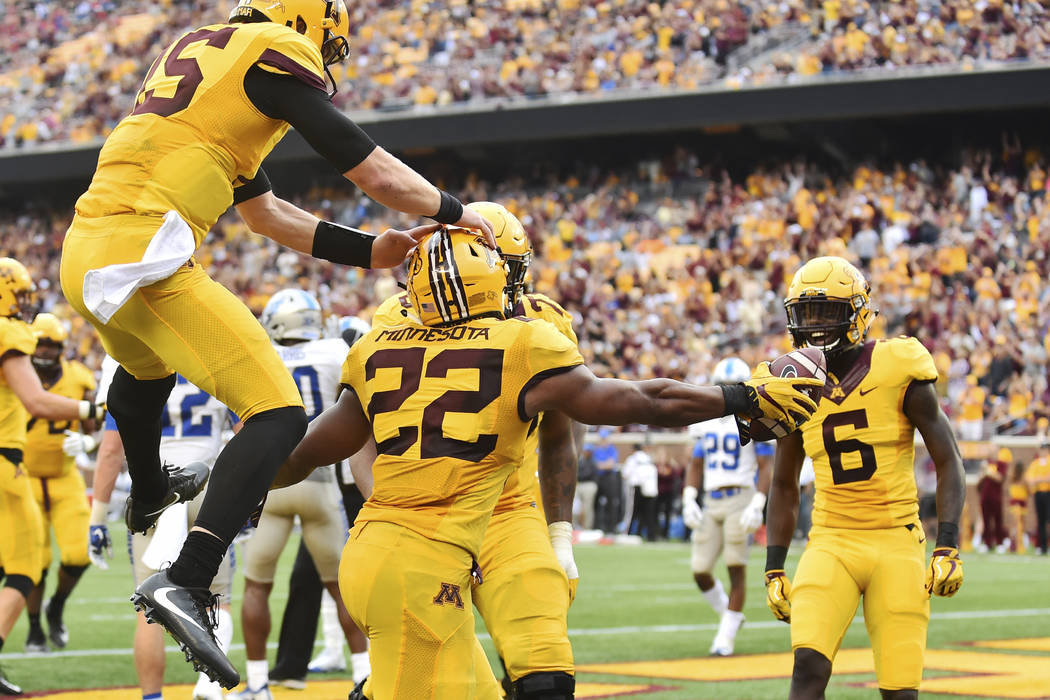 Minnesota running back Kobe McCrary (22) is congratulated by teammates after scoring on a 5-yard touchdown against Middle Tennessee during the second half of an NCAA college football game Saturday ...