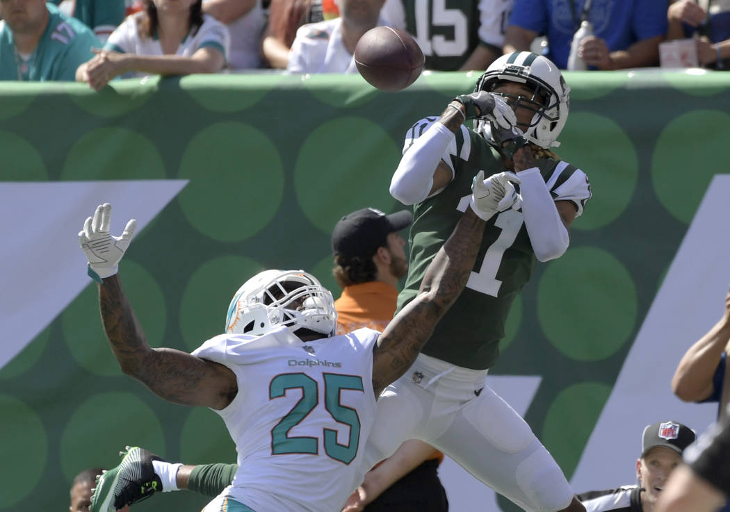Miami Dolphins cornerback Xavien Howard (25) and New York Jets wide receiver Robby Anderson (11) fight for the ball in the end zone during the first half of an NFL football game Sunday, Sept. 24,  ...