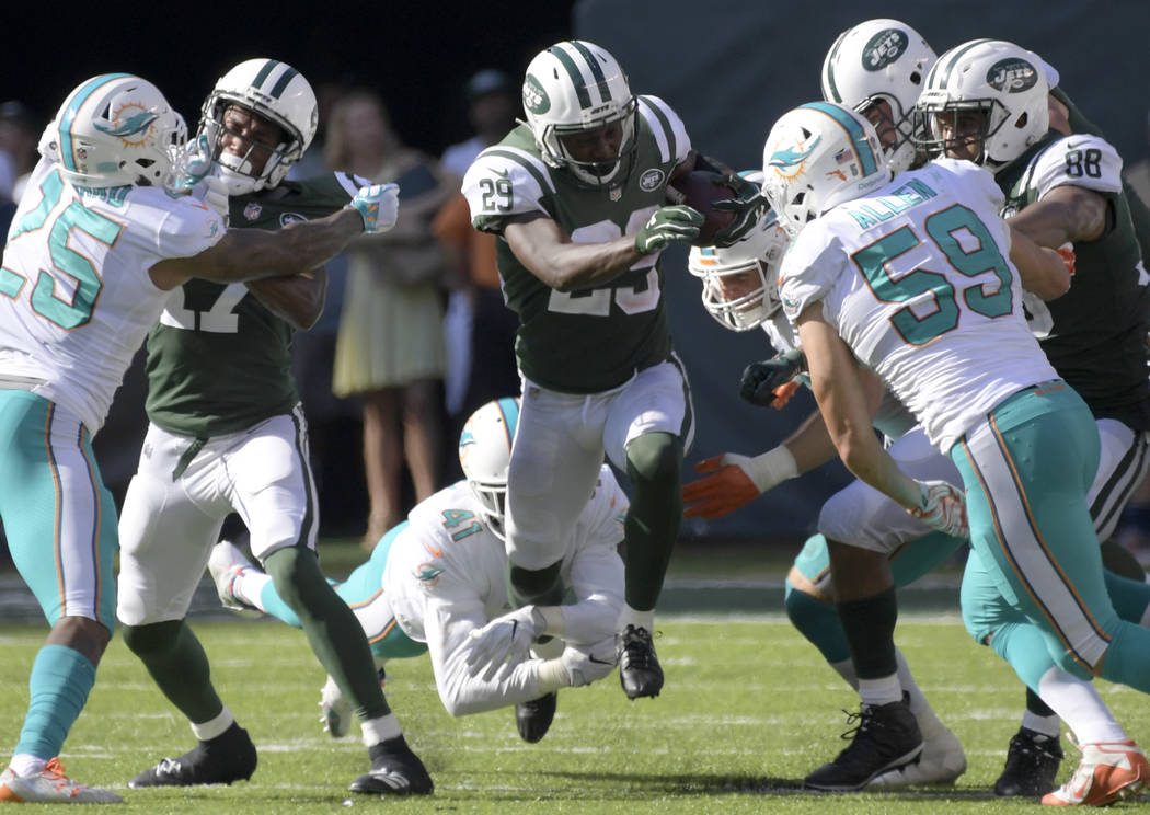 New York Jets running back Bilal Powell (29) attempts to break a tackle by Miami Dolphins cornerback Byron Maxwell (41) during the second half of an NFL football game Sunday, Sept. 24, 2017, in Ea ...