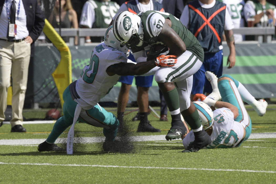 FILE - In this Sunday, Sept. 24, 2017, file photo, New York Jets' Lawrence Thomas (97) tackled by Miami Dolphins' Reshad Jones (20) during the second half of an NFL football game in East Rutherfor ...
