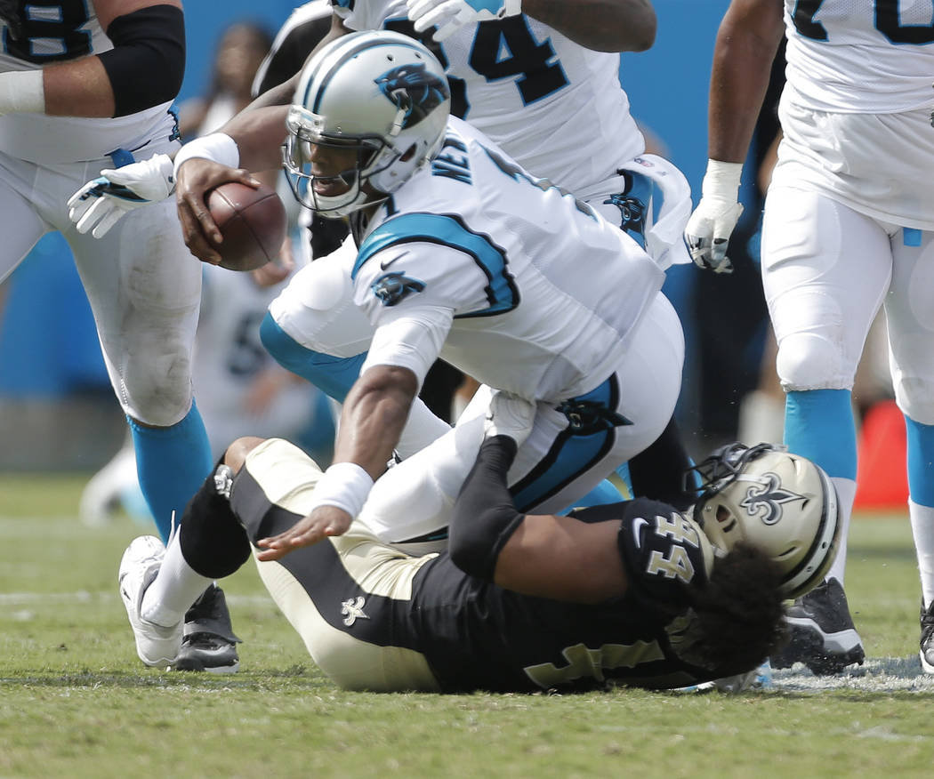 Carolina Panthers' Cam Newton (1) is sacked by New Orleans Saints' Hau'oli Kikaha (44) in the second half of an NFL football game in Charlotte, N.C., Sunday, Sept. 24, 2017. (AP Photo/Bob Leverone)
