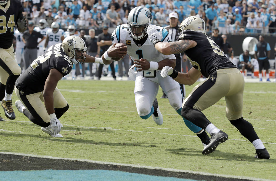 Carolina Panthers' Cam Newton (1) runs past New Orleans Saints' A.J. Klein (53) and Craig Robertson (52) for a touchdown in the second half of an NFL football game in Charlotte, N.C., Sunday, Sept ...