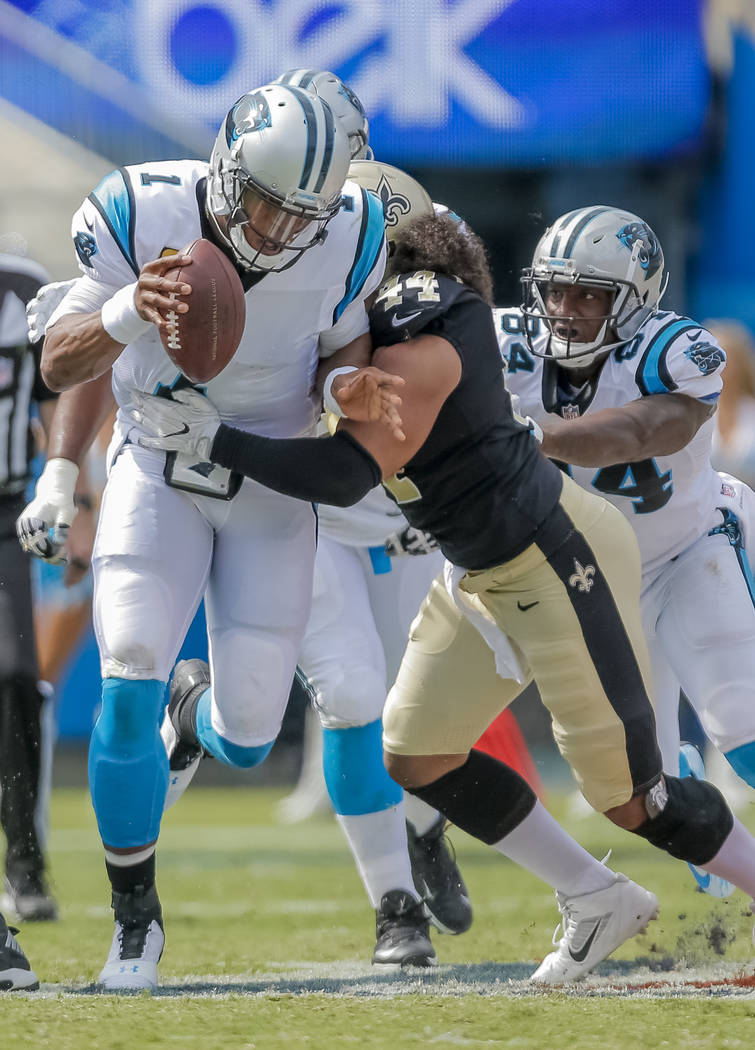 Carolina Panthers' Cam Newton (1) tries to get out of the sack by New Orleans Saints' Hau'oli Kikaha (44) as Ed Dickson (84) tries to help his quarterback during the second half of an NFL football ...