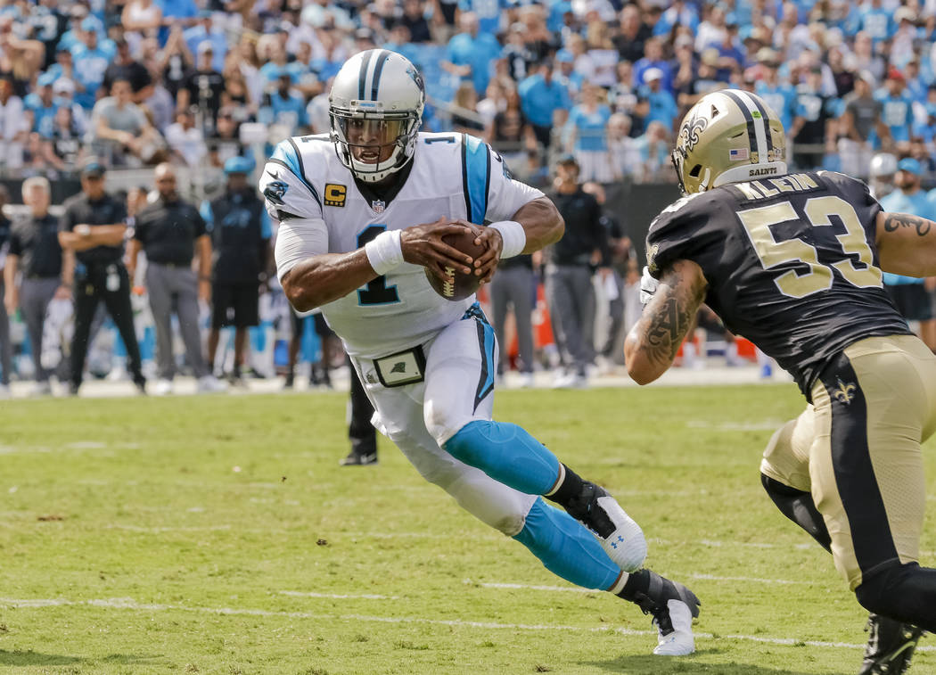 Carolina Panthers' Cam Newton (1) protects the football as he looks past New Orleans Saints' A.J. Klein (53) for the end zone on this touchdown run during the second half of an NFL football game i ...