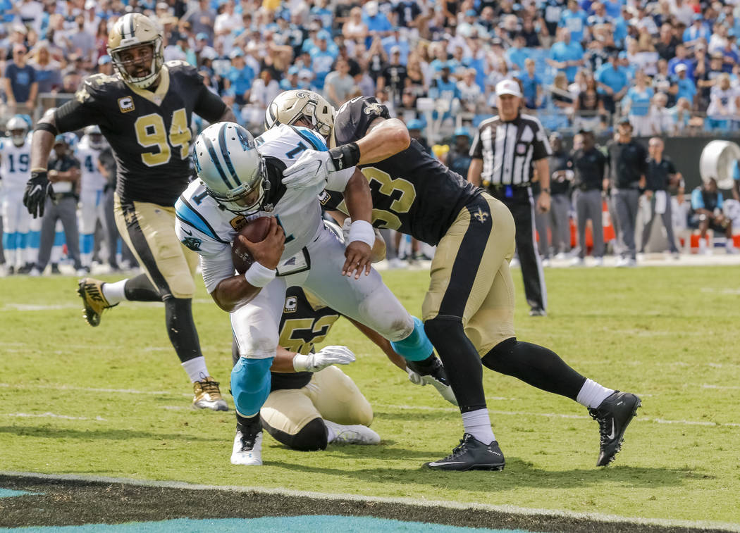 Carolina Panthers' Cam Newton (1) protects the football as he falls into the end zone despite the efforts of New Orleans Saints' A.J. Klein (53), Craig Robertson (52) and Cameron Jordan (94) on th ...