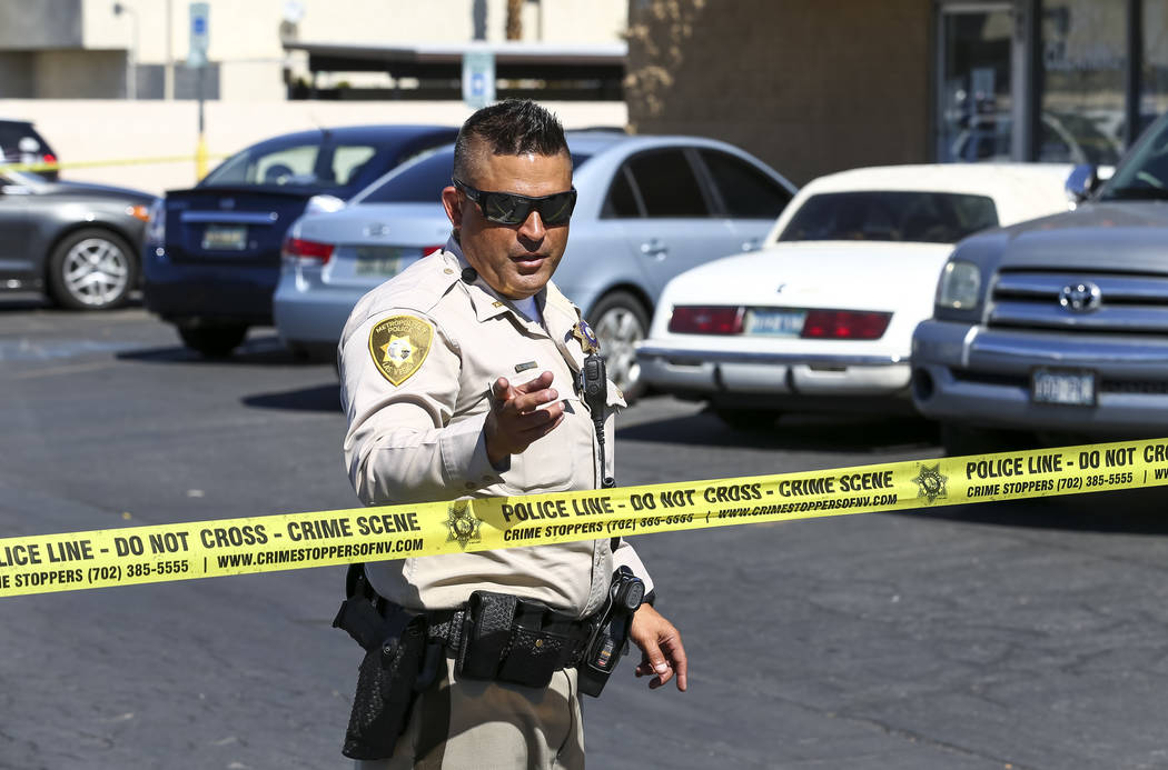 A Metropolitan police officer keeps an eye on the media as they investigate an officer-involved shooting that occurred in a strip mall near Jones Boulevard and U.S. Highway 95 on Thursday, Sept. 2 ...