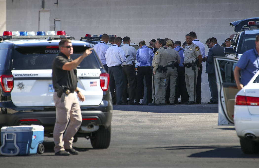 Metropolitan Police and detectives meet at the perimeter of a scene as they investigate an officer-involved shooting that occurred in a strip mall near Jones Boulevard and U.S. Highway 95 on Thurs ...