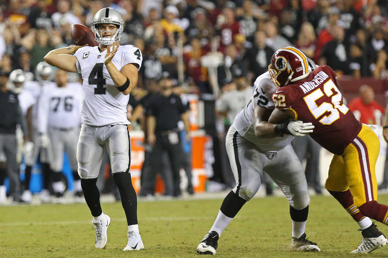 Sep 24, 2017; Landover, MD, USA; Oakland Raiders quarterback Derek Carr (4) throws the ball as Washington Redskins outside linebacker Ryan Anderson (52) chases in the fourth quarter at FedEx Field ...