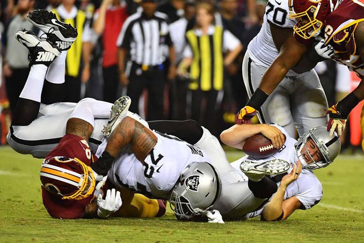 Sep 24, 2017; Landover, MD, USA; Oakland Raiders quarterback Derek Carr (4) is sacked by Washington Redskins linebacker Preston Smith (94) during the first half at FedEx Field. Mandatory Credit: B ...