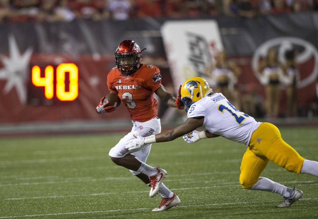 UNLV Rebels running back Lexington Thomas (3) carries the ball as he stiff arms San Jose State Spartans safety Chandler Hawkins (25) during the second half of an NCAA college football game between ...